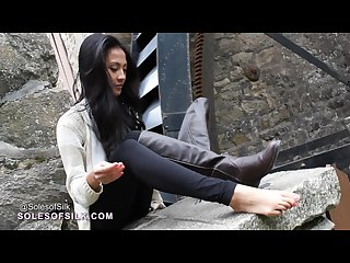 Aliza showing and touching her feet by the mill