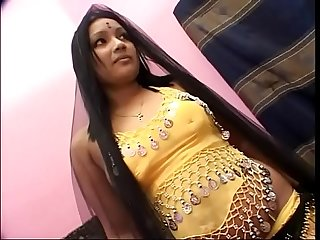 Indian girl Rupa blows a white pole in her yellow beaded top