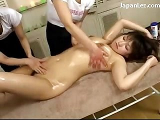 2 masseuse girls rubbing oil to girls breasts and body fingering her pussy