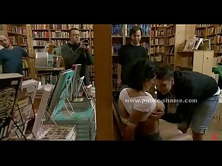 Busty brunette slave in public library