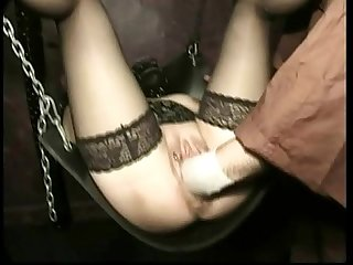 Hot slave with her legs spread in a dungeon and pussy lips pierced gets fucked with a fist