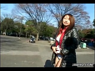 Asian floozy taking off her clothes in public