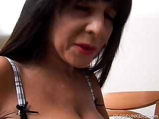 Beautiful busty older brunette strips and talks dirty